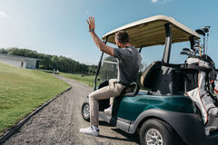 Man waving to friends while riding golf cart before game Royalty Free Stock Photo