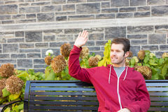 Man waving to somebody from a bench Royalty Free Stock Photo