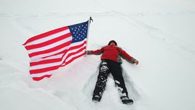 Man is waving US flag lies in the snow. At winter stock video
