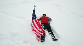 Man is waving US flag lies in the snow. At winter stock video footage
