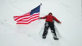 Man is waving US flag lies in the snow. At winter stock footage