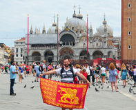 Man waving Venice flag. VENICE ITALY 06 12 2011: Man waving Venice flag in front the Patriarchal Cathedral Basilica of Saint Mark the cathedral church of the Stock Photos