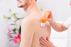 Man at waxing hair removal in beauty parlor. Man receiving waxing for hair removal in beauty parlor Stock Photo