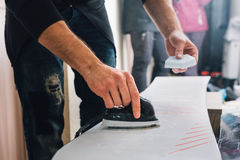 Man is waxing a snowboard. Man is waxing a colorful snowboard with hot iron and wax Stock Photos