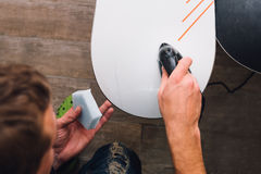 Man is waxing a snowboard. Man is waxing a colorful snowboard with hot iron and wax Stock Photo