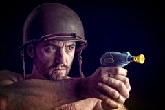 War is not a game. Man wear army helmet and hold little toy gun stock images
