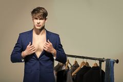 Man wear formal blue suit on bare chest in wardrobe. On grey background. Business fashion, style concept. Clothing, dressing, closet. Shopping, sale, purchase royalty free stock photo