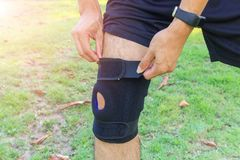 Knee Pads Hole Sports. The man wear the Knee Support Brace Patella with sunlight in the park / Knee Pads Hole Sports Royalty Free Stock Photos