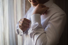 Man wear a shirt and cufflinks, correct clothes, dressing, man's style. Fees groom, wedding preparations, sense of style Stock Photos
