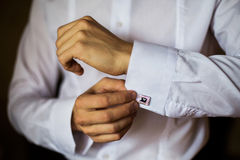 Man wear a shirt and cufflinks, correct clothes. Dressing, man's style, fees groom, wedding preparations, sense of style, correcting sleeves Stock Images