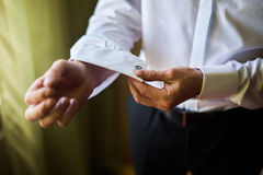 Man wear a shirt and cufflinks, correct clothes, dressing. Man's style, fees groom, wedding preparations, sense of style, correcting sleeves Stock Images