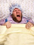 Man weared as baby in bed Royalty Free Stock Images