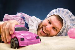 Man weared as baby with car Royalty Free Stock Photo