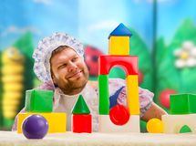 Man weared as baby play indoor Stock Image