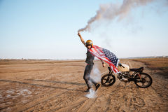 Man wearing american cape and golden helmet holding smoke bomb Royalty Free Stock Photos