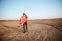Man wearing american flag cape and golden helmet walking away Royalty Free Stock Photos