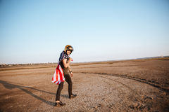 Man wearing american flag cape and golden helmet walking Royalty Free Stock Photos