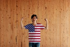 Man wearing American flag color of shirt and standing with raised both fist. On the wooden wall background royalty free stock photography