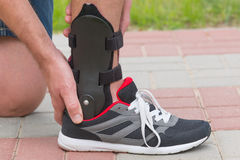 Man wearing ankle brace. Man in athletic sneakers checking his ankle orthosis or brace on the street stock images