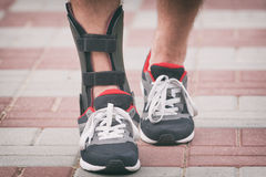 Man wearing ankle brace. Man in athletic sneakers wearing ankle orthosis or brace royalty free stock photos