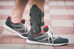 Man wearing ankle brace. Man in athletic sneakers wearing ankle orthosis or brace Stock Photo