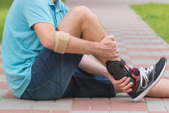 Man wearing ankle brace. Man in athletic sneakers sitting on the street and checking his ankle orthosis or brace stock images