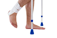 Man Wearing Ankle Brace Walking with Crutches. Close Up Side View Profile of Man with Bare Feet Wearing Supportive Ankle Brace and Walking with Crutches in Stock Photography