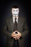Man wearing  anonymous mask stands against dark background Royalty Free Stock Photography