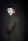 Man wearing  anonymous mask turned away and stands against dark background Stock Photo