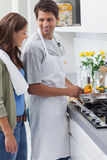 Man wearing apron and cooking Royalty Free Stock Image