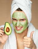 Man wearing avocado face mask and showing thumbs up Stock Photos