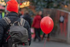 Man wearing backpack and red hat on street with balloon stock images