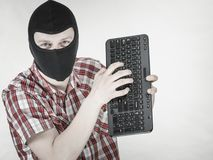 Man wearing balaclava holding keyboard stock images