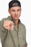 Man wearing baseball hat backwards and pointing Stock Photo
