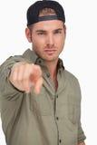 Man wearing baseball hat backwards and pointing Stock Photo