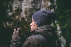 Man Wearing Beanie Holding Smartphone stock images