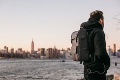 Man Wearing Black Bubble Jacket and Black Leather Backpack Near Bay Royalty Free Stock Photo