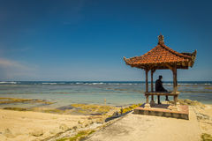 Man wearing a black clothes in a beautiful sunny day under a small cabain in the beach of Pantai pandawa, in Bali island. Indonesia Royalty Free Stock Images