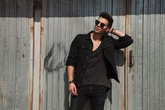 Man wearing black clothes fixes his hair near garage door. Man wearing black clothes fixes his hair near a garage door, outside, portrait picture stock image