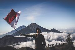 Man Wearing Black Crew-neck Sweater Holding White and Red Flag Standing Near Mountain Under Blue and White Sky stock images