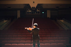 Man Wearing Black Formal Suit Jacket and Black Pants Playing Violin on Front of Red Seat Theater Royalty Free Stock Photography