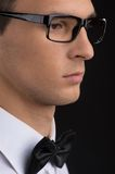 Man wearing black glasses on dark background. Stock Image
