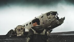 Man Wearing Black and Gray Hoodie Jacket Near Airplanes Crashed Stock Photography