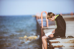 Man Wearing Black and Green Hoodie Sitting on Brown Flooring Near Body of Water during Daytime Royalty Free Stock Photo