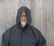 Man Wearing a Black Hooded Cape. A bearded man wearing a black hooded cape Stock Photos