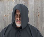 Man Wearing a Black Hooded Cape One Eye. A bearded man wearing a black hooded cape with one eye showing Stock Image