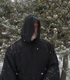 Man Wearing a Black Hooded Cape Snow Falling. A grey bearded man wearing a black hooded cape with snow falling Stock Photography