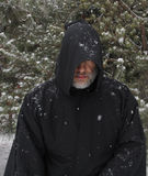 Man Wearing a Black Hooded Cape Snow Falling no Eyes. A grey bearded man wearing a black hooded cape with snow falling and no eyes visible stock image