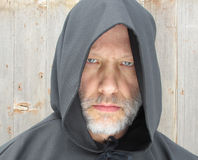 Man Wearing a Black Hooded Cape Staring. A bearded man wearing a black hooded cape with two eyes staring at viewer Stock Image