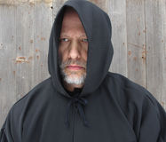 Man Wearing a Black Hooded Cape Two Eyes. A bearded man wearing a black hooded cape with two eyes showing royalty free stock image